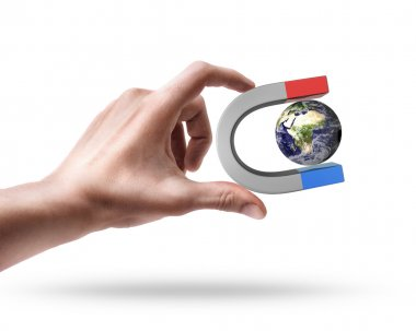 Man's hand holding Magnet and Earth