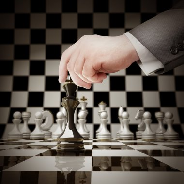 Hand holding white chess figure on chess board