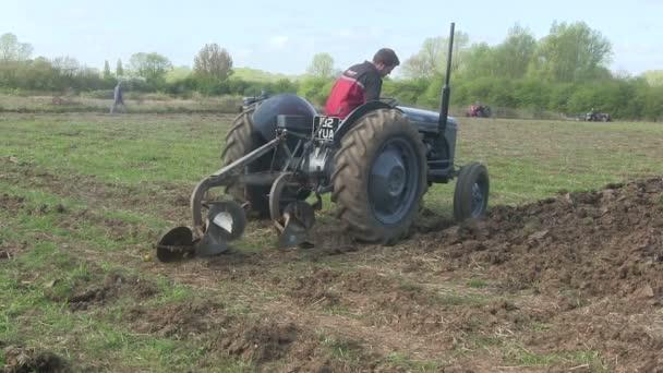szürke vintage traktor húzza egy eke.