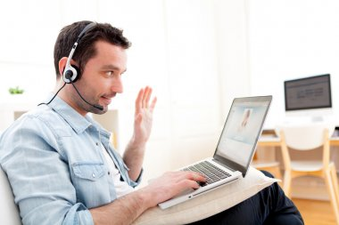 Young relaxed man video-calling on Internet