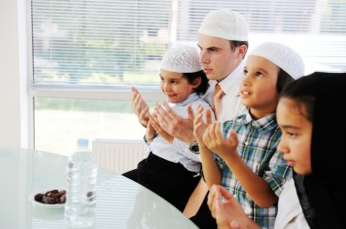 Muslim father praying with kids for Ramadan