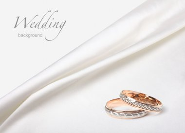 Wedding rings on white silk background