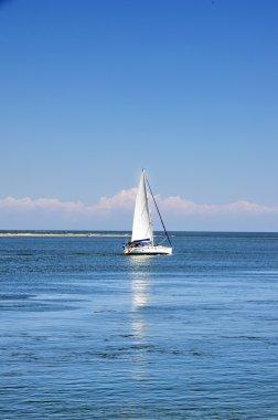 White sailboat in blue sea