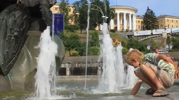 Junge Spritzwasser durch Brunnen