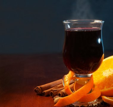 Mulled wine with orange and spices on dark background
