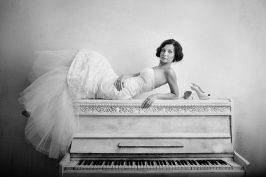 Beautiful woman in luxurious dress lying on the piano. Retro style