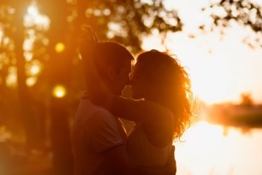 young beautiful couple embracing on a white background of a sunset