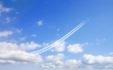 Airplane flys in white clouds in a blue sky and leaving trail