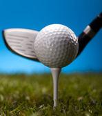 golfový míček na zelené trávě na modrém pozadí