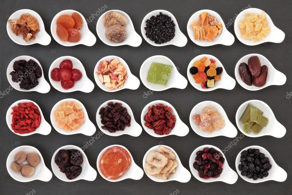 Large dried fruit selection in white bowls over slate background.