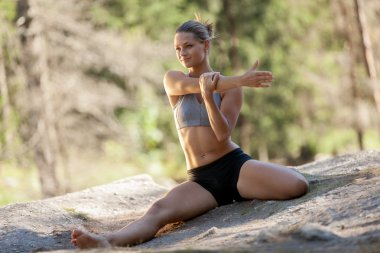 Gorgeous blonde woman doing stretching exercises while sitting o