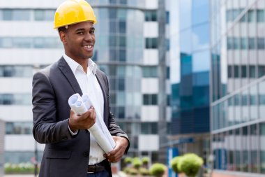 Afro american construction engineer in front of building holding blueprints stock vector