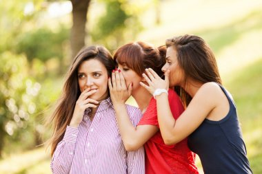 Three woman are whispering