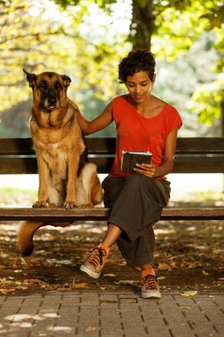 Woman on a bench with digital tablet and dog