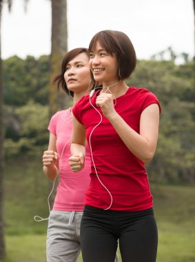 asian girls jogging outdoor while listening to music