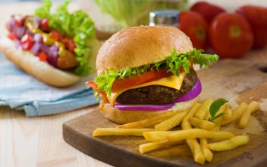 burger and french fries with fast food ingredients on the backgr