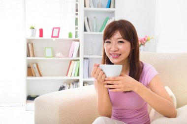 Chinese Asian female enjoying cup of coffee