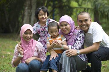malay muslim family having fun in the park