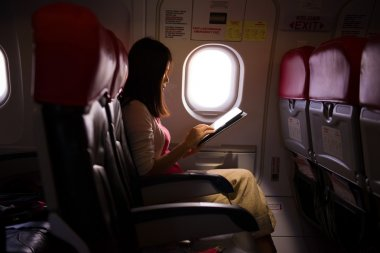 Female lonely traveling on plane while reading on seats during a