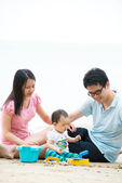 Asijské rodiny na pláži