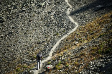 Man walking on mountain trail, hiking to the top