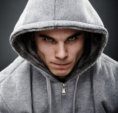 Close-up portrait of threatening gangster wearing a hoodie, representing the concept of danger stock vector