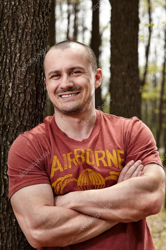 Handsome man leaning on a tree trunk