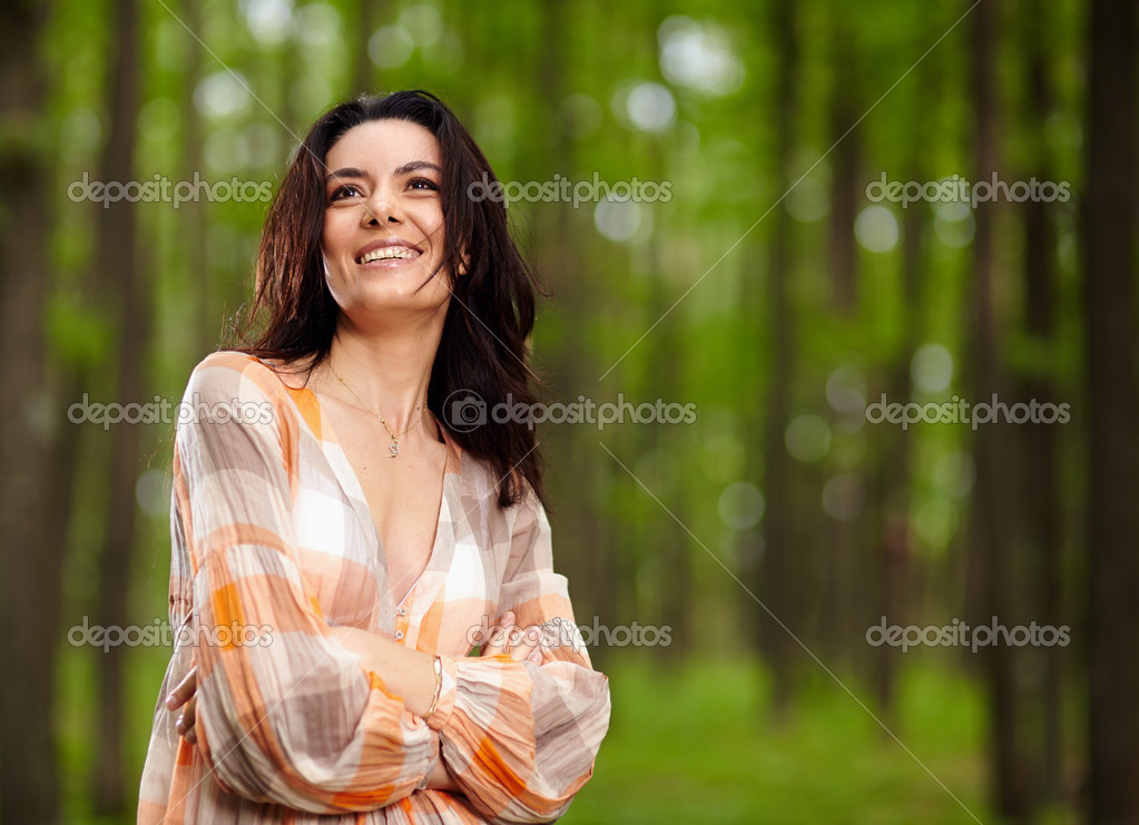 Beautiful woman with arms folded in a forest