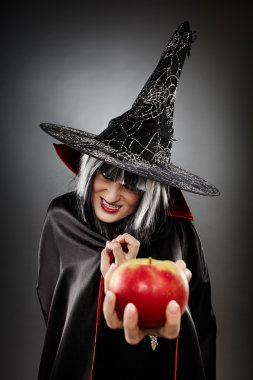 Witch offering a poisoned apple