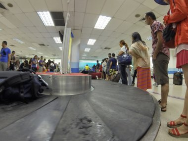 People waiting for their bags at airport conveyor belt