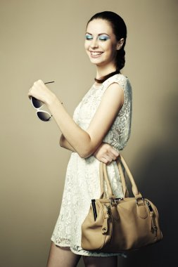 Portrait of young smiling woman with a leather bag