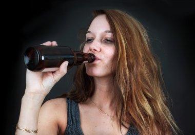 Drunk woman drinking beer over black