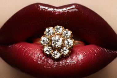 Close-up of beautiful woman's lips with bright fashion dark red glossy makeup. Macro lipgloss cherry make-up. Mouth with wedding gold diamond ring
