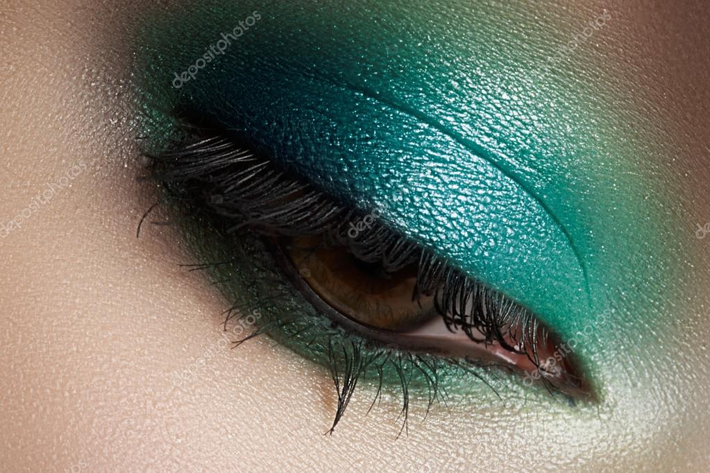 Elegance close-up of female eye with mint color eyeshadow. Macro shot of beautiful woman's face part. Wellness, cosmetics and make-up