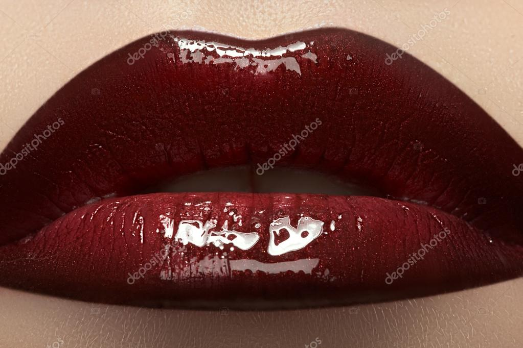 Close-up of woman's lips with bright fashion dark red glossy makeup. Macro lipgloss cherry make-up