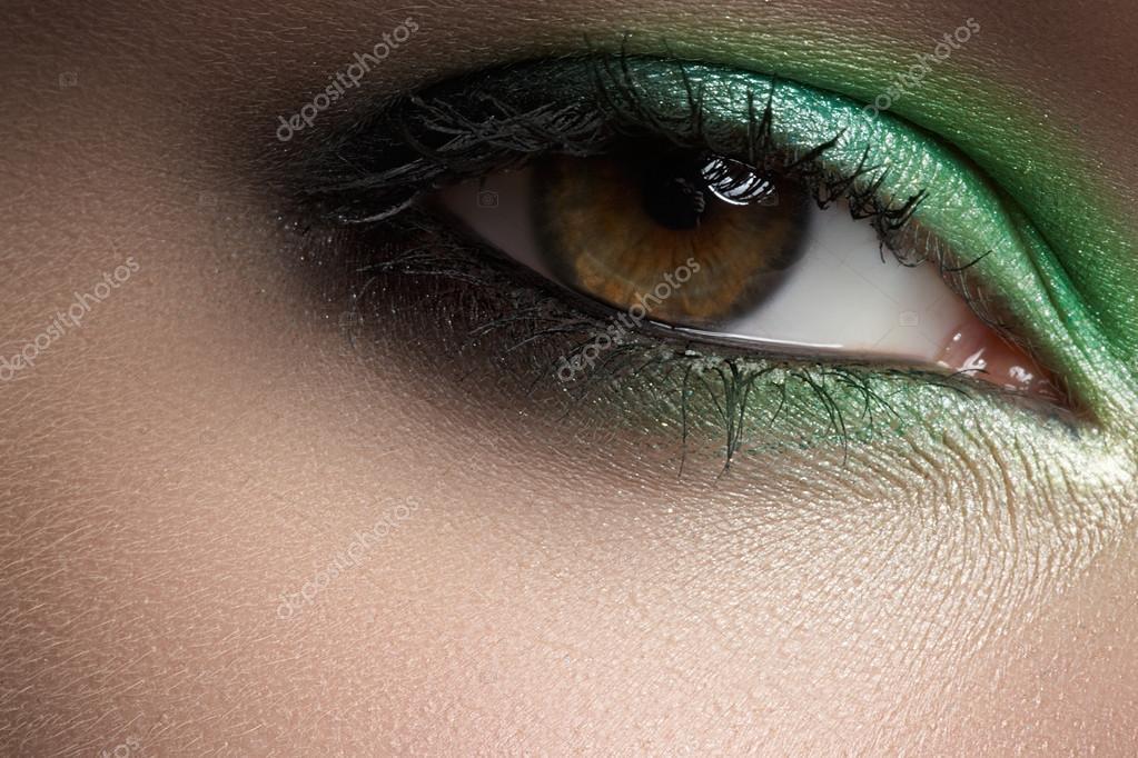 Elegance close-up of female eye with green smoky eyeshadow. Macro shot of face part