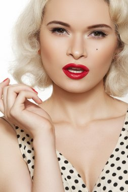 Fashion portrait of beautiful woman model with red lips make-up and long curly blond hair on white background. Pin-up retro style