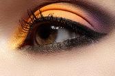 Eleganz Nahaufnahme des weiblichen Auges mit festlichem Lidschatten in heller Farbe. Makroaufnahme der schönen Gesichtspartie der Frau. Wellness, Kosmetik und Make-up. Schicke Urlaubsidylle