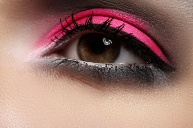 Elegance close-up of female eye with celebratory bright color eyeshadow. Macro shot of beautiful woman's face part. Wellness, cosmetics and make-up. Vibrant pink & black colours in visage