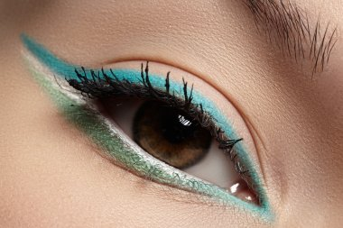 Elegance close-up of beautiful female eye with fashion trend mint colors eyeshadow and eyeliner. Macro shot of beautiful woman's face part with makeup. Cosmetics, beauty and make-up