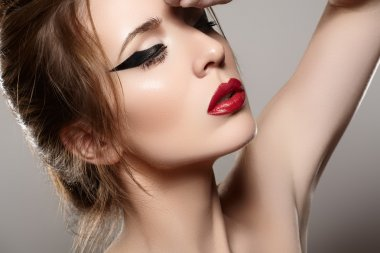 Close-up portrait of sexy caucasian young woman model with glamour red lips make-up, eye arrow makeup, purity complexion. Perfect clean skin