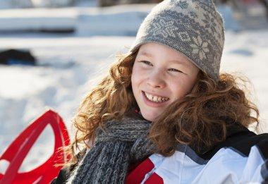 Smiling blond girl in winter park