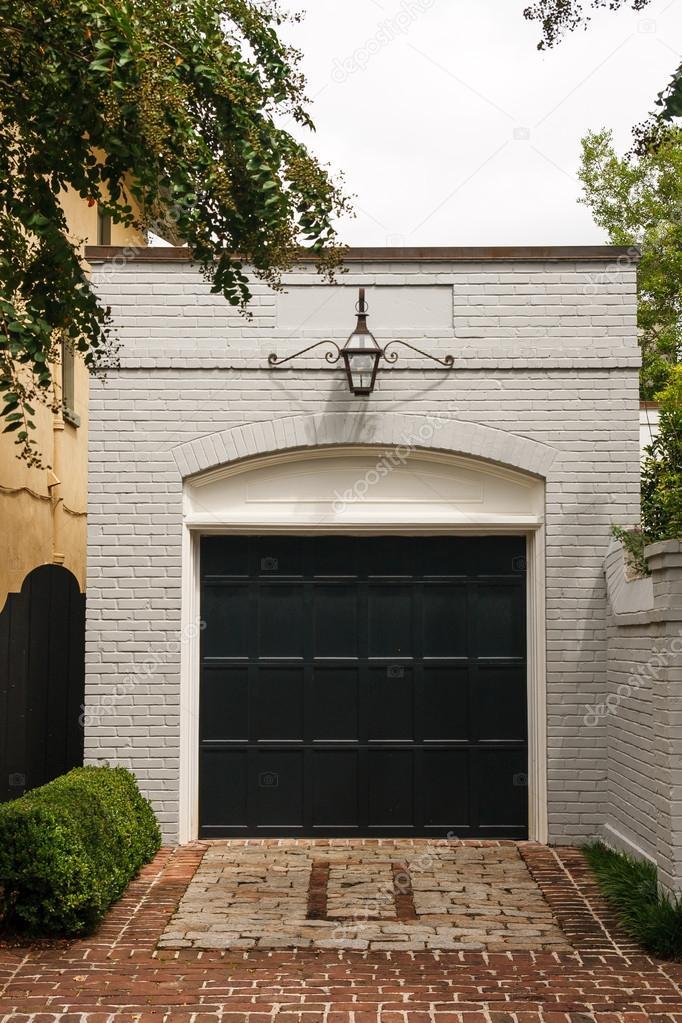 white brick garage with black door stock photo. Black Bedroom Furniture Sets. Home Design Ideas