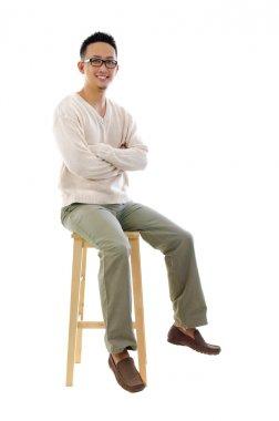 Full body Asian man sitting on a chair