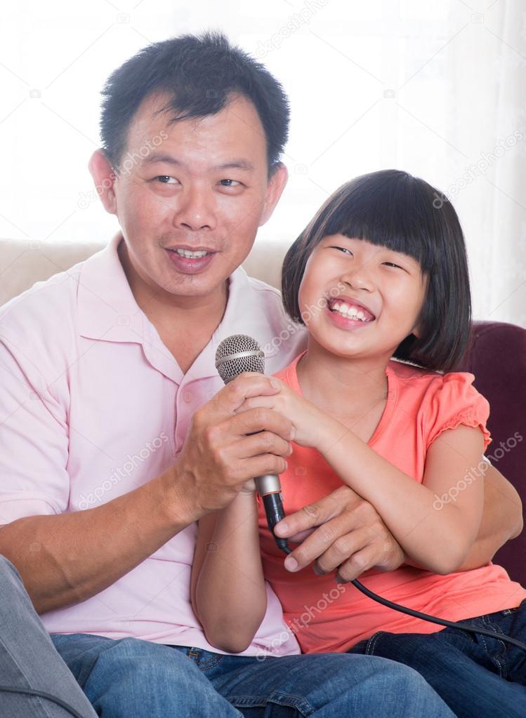 Happy Asian family singing karaoke — Stock Photo © szefei #21708697