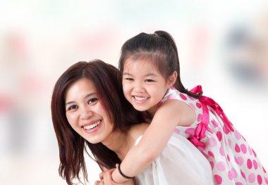 Asian family piggyback ride at home.