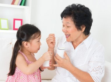 Grandmother and grandchild eating yoghurt
