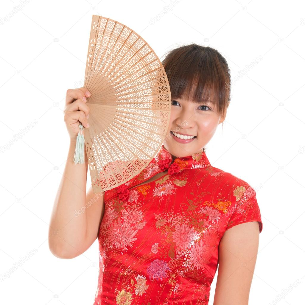 4178e9af3 Asian girl with Chinese traditional dress cheongsam or qipao holding Chinese  fan. Chinese new year concept, female model isolated on white background.