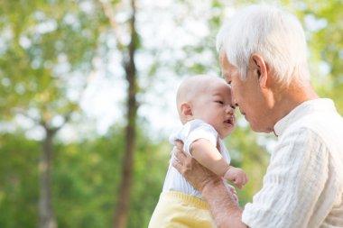 Asian grandfather kissing grandson