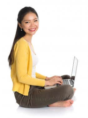 Side view Asian girl using notebook